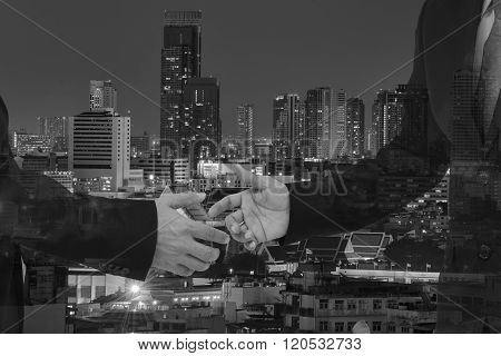 Double exposure of handshake and city black and white.