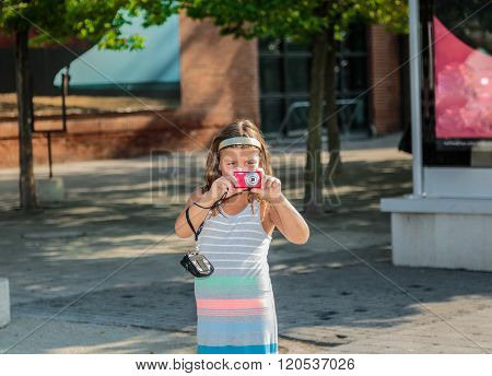 happy little girl standing in outdoor park and taking picture on her small photo camera