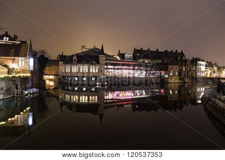 GHENT BELGIUM - 18TH FEBRUARY 2016: A view of the outside of the De Oude Vismijn restaurant showing reflections in the river Leie at night.