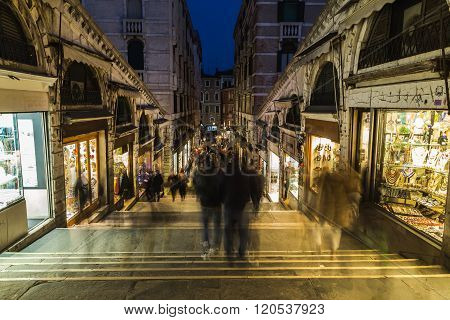 VENICE ITALY - 14TH MARCH 2015: A view of shops and streets along Rialto Bridge at night. The blur of people can be seen.