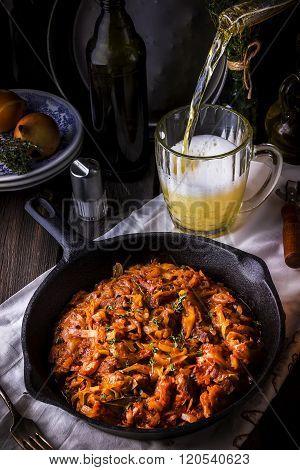 Stewed Cabbage  In A Vintage Frying Pan And Beer Pouring In Mug On Wooden Table.