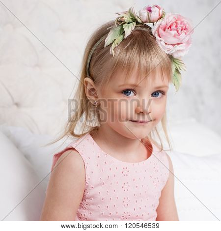 Portrait Of A Little Blonde Girl  Sitting On The Bed In The Room