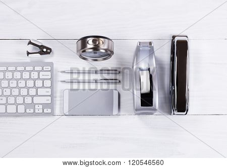 Silver Colored Stationery Objects On White Wood Background