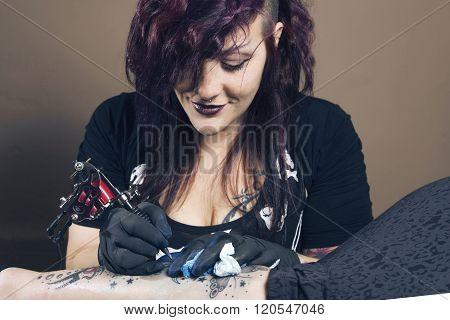 Female Tattoo Artist Works On A Tattoo.