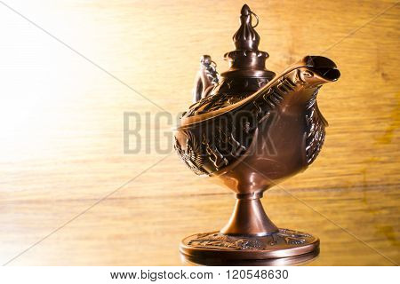 Aladdin's lamp isolated on bright and light brown  background