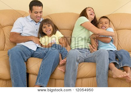 Family tickling each other on the sofa