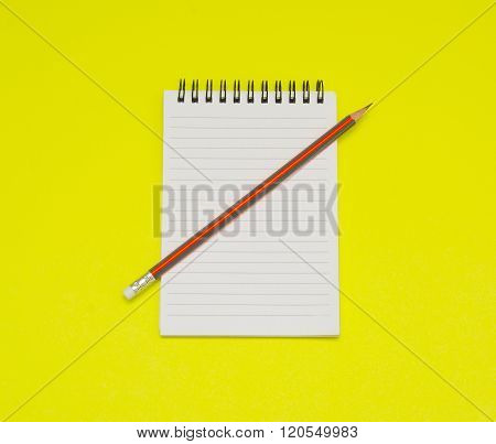 Notebook and pencil on the yellow background