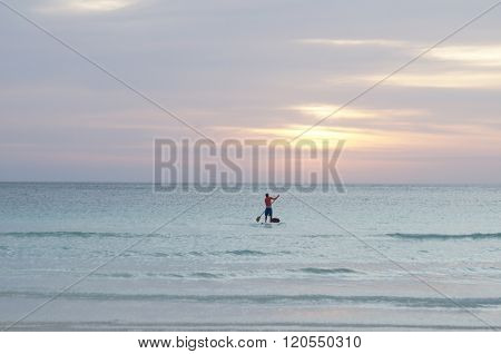 Person paddle boarding during sunset