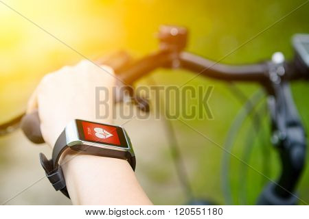 Woman Riding A Bike With A Smartwatch Heart Rate Monitor.