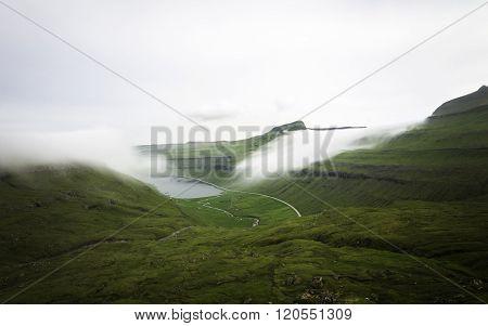 Fog lying on mountains. Faroe islands, Denmark, Europe. Long Exposure