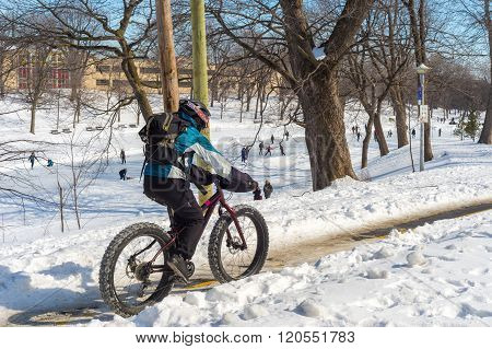 A Person Is Riding A Fat Tire Snow Bike In Winter.