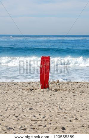 Lone red surfboard on beach with waves