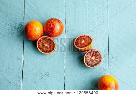Several sanguine oranges on blue wooden background