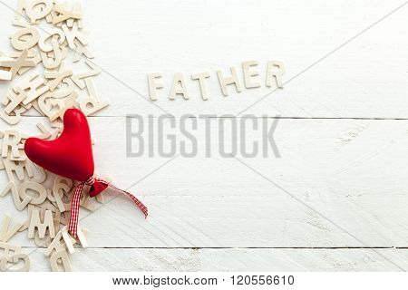 Scattered wooden letters and a red heart
