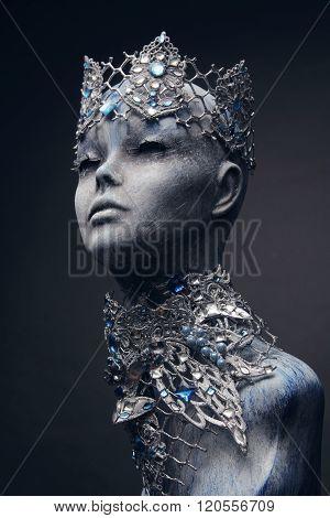 Mannequin in creative silver snow queen crown and collar on dark background