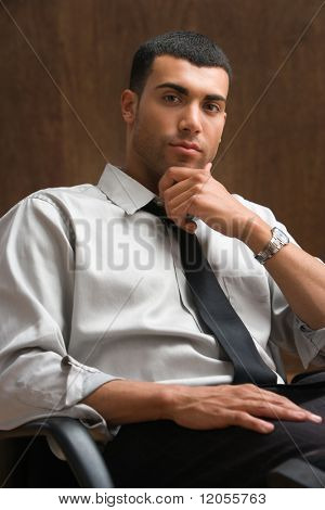 Portrait of businessman sitting with hand on chin