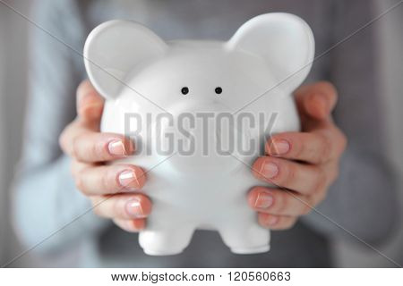 Woman holding in hands white piggy bank