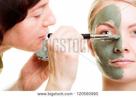Cosmetician Applying Clay Facial Mask At Woman Face.