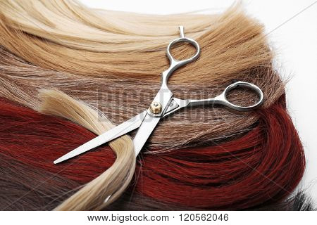 Hairdresser's scissors with varicolored strands of hair on background