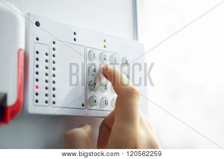 Security alarm keypad with male hand, closeup