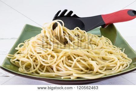 Al Dente Spaghetti Pasta On A Plate With Pasta Fork On White Background