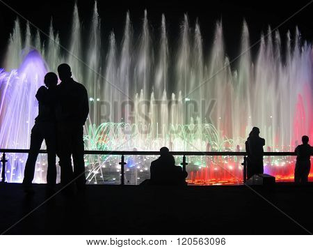 Lovers Silhouettes Against Fountain