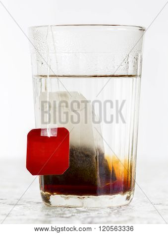Faceted Glass Of Boiled Water And Tea Bag