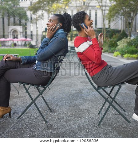 Friends talking on cell phone in park