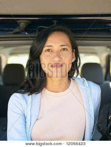 Woman posing from inside SUV hatch