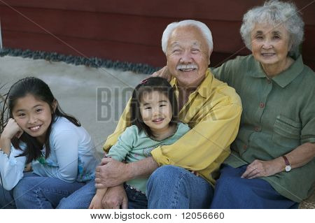 Senior couple smiling with granddaughters