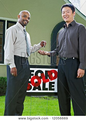 Man handing the keys to a new house to owner