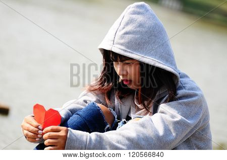Broken Hearted Girl Seeing Red Paper Heart