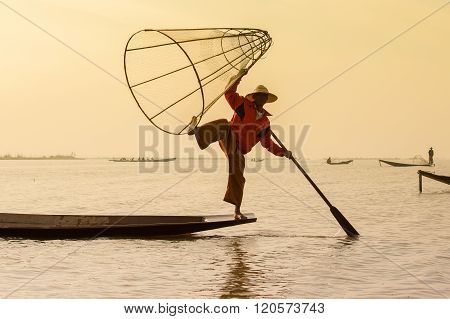 INLE LAKE MYANMAR - JANUARY 12 2016: Unidentified Burmese fisherman on bamboo boat catching fish in traditional way with handmade net. Inle lake Myanmar Burma