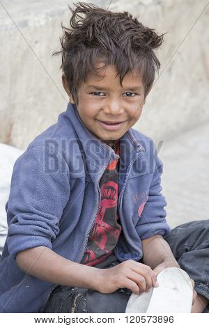 LEH INDIA - SEPTEMBER 08 2014: Unidentified beggar boy begs for money from a passerby in Leh. Poverty is a major issue in India