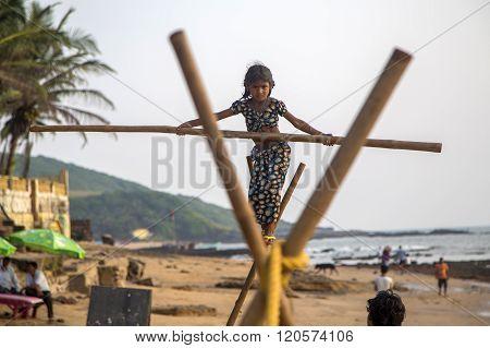 ANJUNA, INDIA - OCTOBER 14, 2015: Unidentified Goan Girl on a tightrope at the Anjuna Beach.