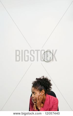 Businesswoman sitting on a chair with her hands on her cheeks