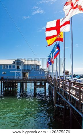 Santa Barbara, U.S.A. - June 1, 2011: The Sterns Wharf  built on stilts and flags on the sea front.