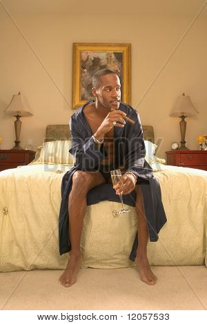 Man with cigar and champagne in bedroom
