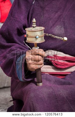 Old Tibetan Woman Holding Buddhist Prayer Wheel In Lamayuru Gompa, , Ladakh, India.