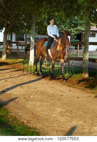 Happy woman horseback riding at farm.