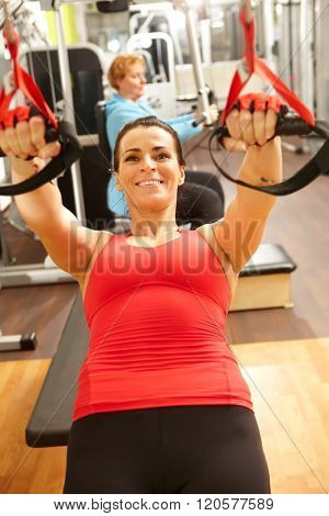 Sporty woman doing TRX suspension training in gym, smiling.