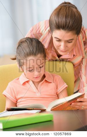 Mother looking over shoulder of daughter who is reading