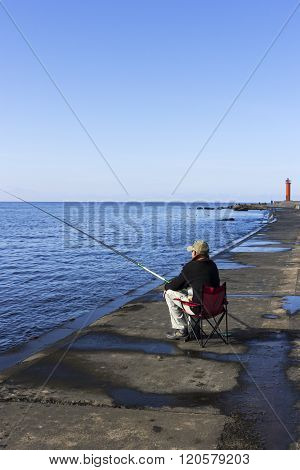 Fisherman Near The Lighthouse In Riga, Latvia