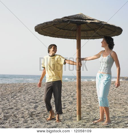Young couple laughing underneath umbrella on beach