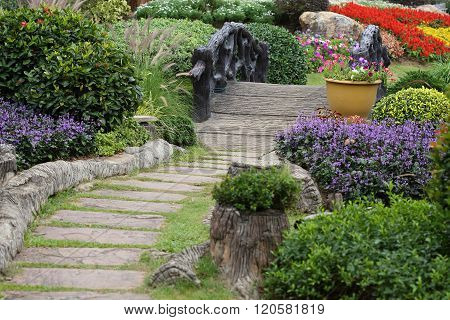 Landscape Of Floral Gardening With Pathway And Bridge In Garden