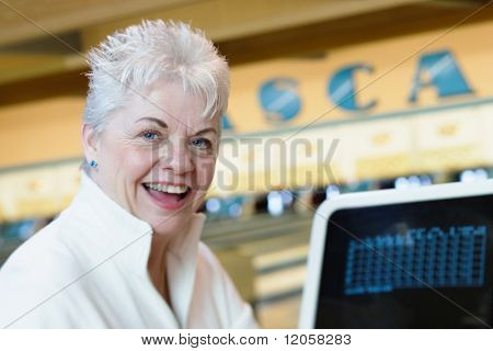 Portrait of woman keeping score at bowling alley