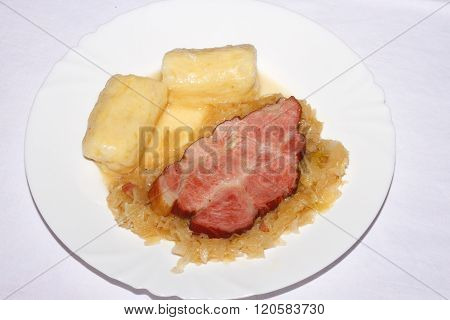 A slice of roast pork with potato dumplings and pickled cabbage on a plate