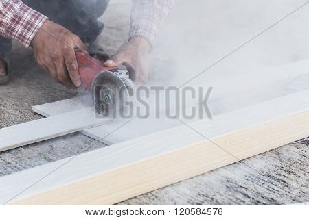 Carpenter Hands Using Electric Saw On Wood At Construction Site