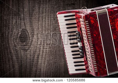 Part red accordion on wooden grey background. Write text