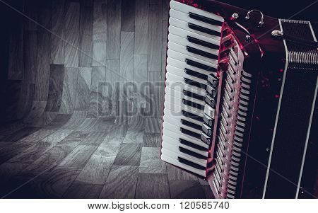 Part pink accordion on wooden grey background. Write text